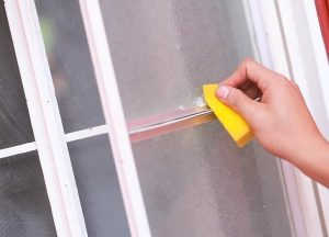 Enlever les traces de colle sur une vitre avec de l'eau chaude savonneuse